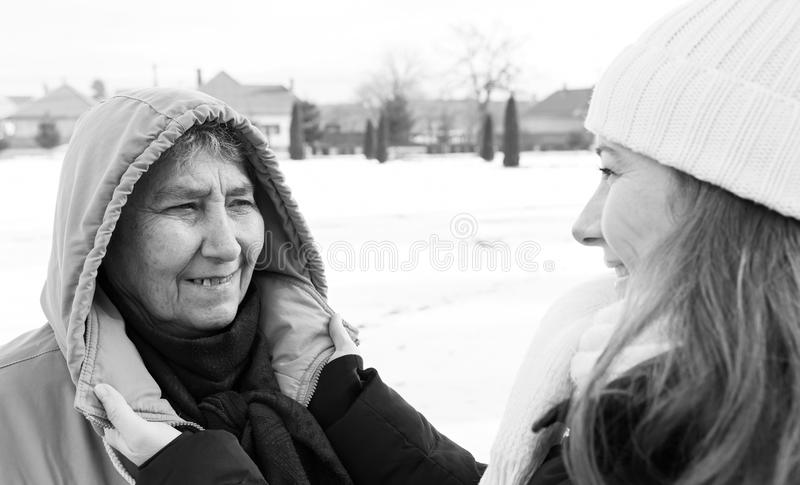 Smiling elderly woman and young caregiver. Photo of happy elderly women and young caregiver stock images