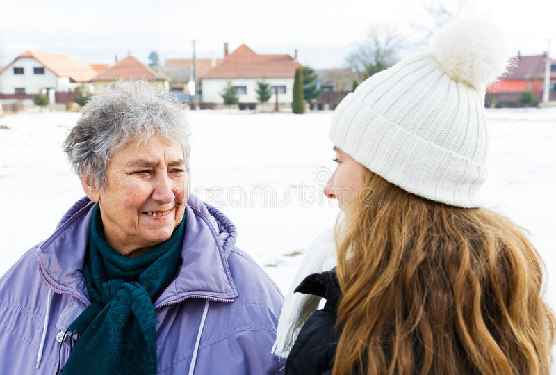 Smiling elderly woman and young caregiver. Photo of happy elderly women and young caregiver royalty free stock images