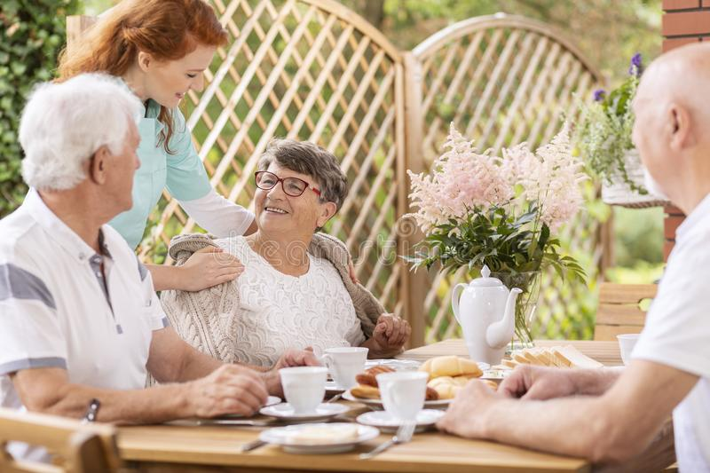 Smiling elderly woman eating breakfast with friends and her care. Smiling elderly women eating breakfast with friends and her caregiver behind her royalty free stock images