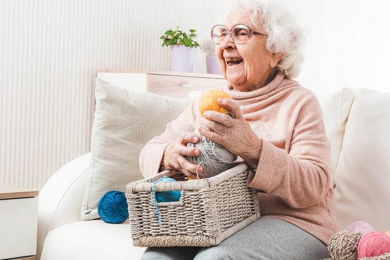 Smiling eldery woman holding colorful laces balls. Smiling eldery woman with white basket holding colorful laces balls stock image