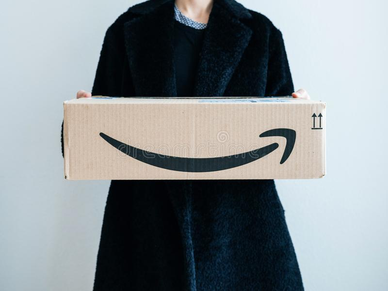Smiling elegant fashionista woman holding Amazon Prime stock images