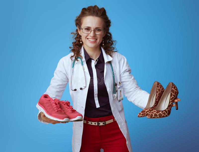 Medical doctor woman showing sneakers and high heel shoes. Smiling elegant medical doctor woman in bue shirt, red pants and white medical robe showing fitness stock photography