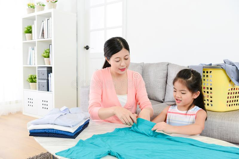 Smiling elegant mother teaching little daughter stock photography