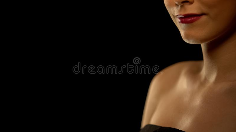 Smiling elegant woman isolated on black background, place for text, statistics royalty free stock photo