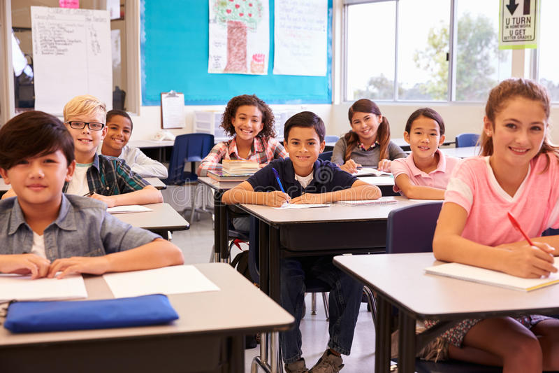 Smiling elementary school kids sitting at desks in classroom royalty free stock image