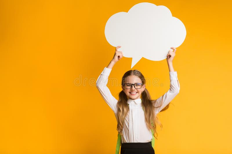 Smiling Elementary Student Girl Holding Speech Bubble Overhead, Studio Shot. Smiling Elementary Student Girl Holding Speech Bubble Overhead On Yellow Studio stock photos