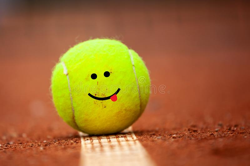 Smiling emoji on tennis ball lies on the clay court stock images