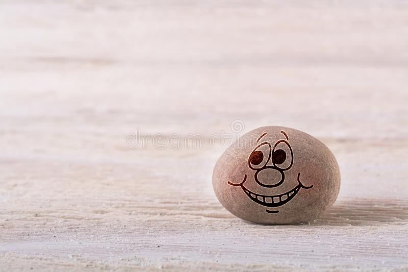 Smiling emoticon. Stone face on white wood background with free space for your text royalty free stock image
