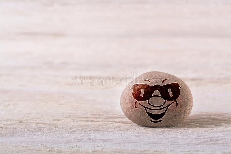 Smiling emoticon with sunglasses. Stone face on white wood background with free space for your text royalty free stock photos