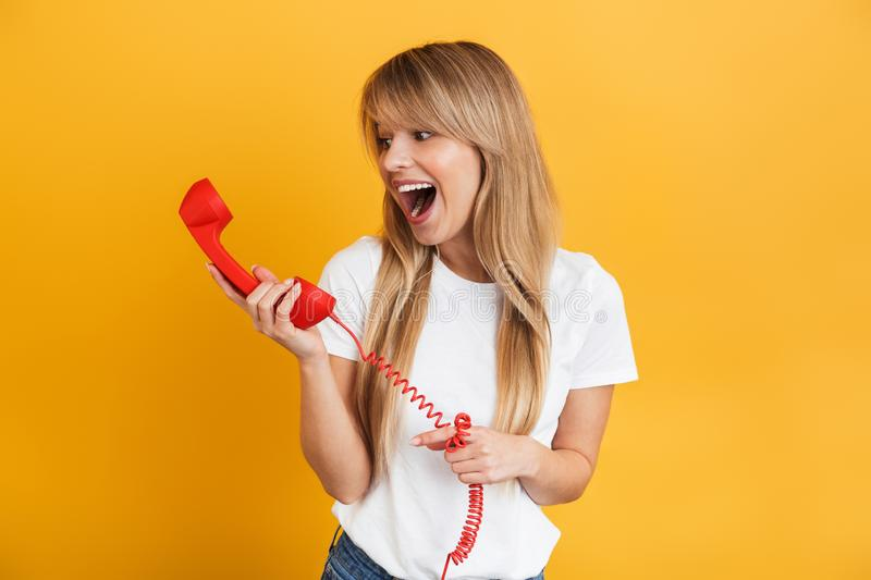 Smiling emotional happy young blonde woman posing  over yellow wall background dressed in white casual t-shirt talking by. Photo of a screaming smiling emotional royalty free stock images