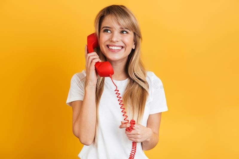 Smiling emotional happy young blonde woman posing isolated over yellow wall background dressed in white casual t-shirt talking by. Photo of a cheerful happy stock photo