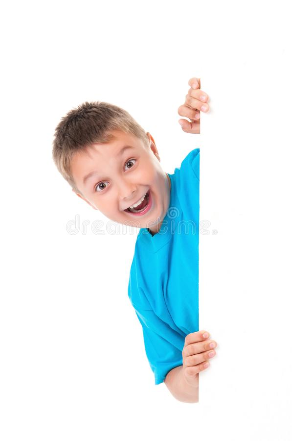 Smiling emotional positive teenager boy in bright blue t-shirt and posing behind a white panel isolated on white background. Place stock image
