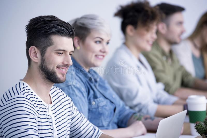 Employee cooperating with friendly team stock images
