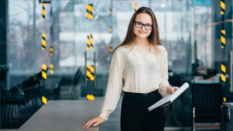 Smiling employee intern workplace hold documents. Friendly employee. Young smiling intern in glasses holding clipboard with documents stand at workplace royalty free stock photography