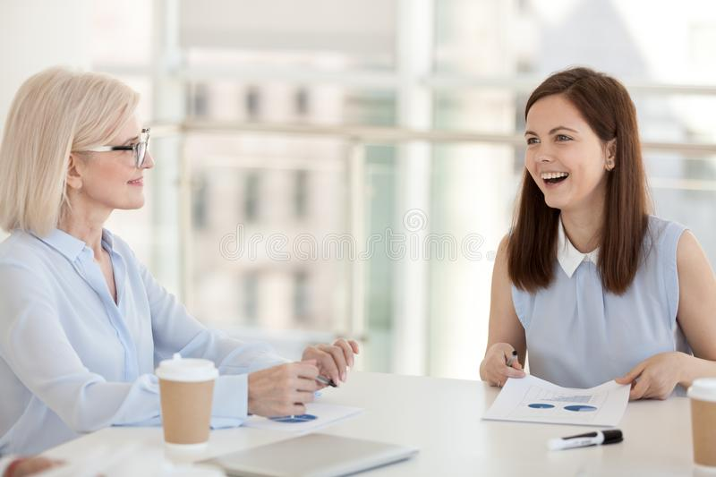 Smiling employees discuss paperwork statistics at company meeting stock photo