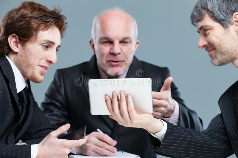 Smiling employees in a discussion with a senior stock image