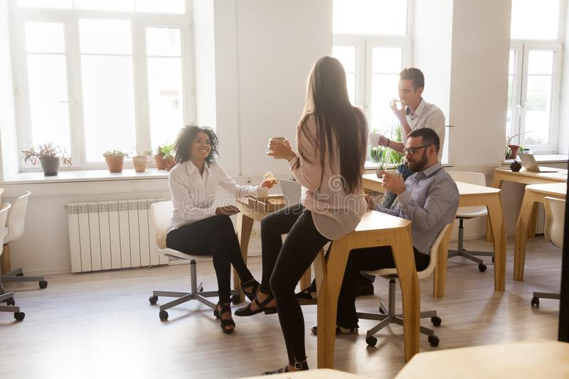Smiling employees enjoying pizza having shared lunch break in of royalty free stock photos