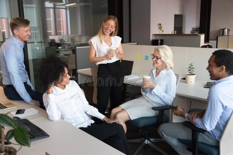 Smiling employees talk at informal meeting in open space. Smiling multiethnic employees talk and chat enjoy drinking coffee at office break, happy diverse royalty free stock images