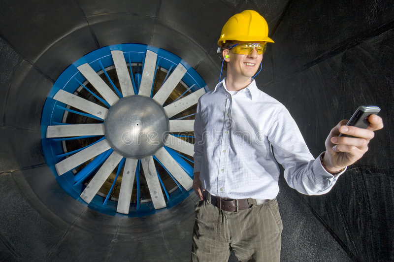 A smiling engineer, looking at his phone stock image