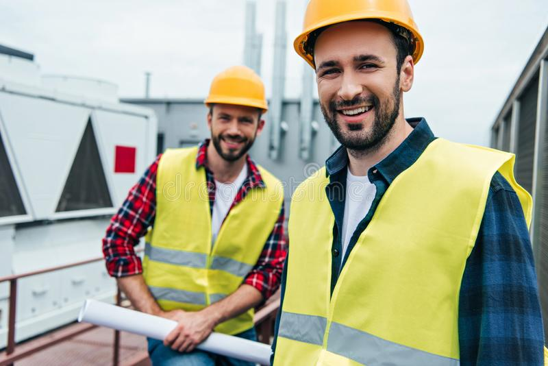 smiling engineers in safety vests and helmets with blueprint royalty free stock photos