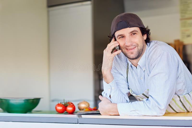 Smiling entrepeneur making a phone call in his takeaway food sta. Entrepeneur smiling while making a call on his phone from his takeaway food business stock photo