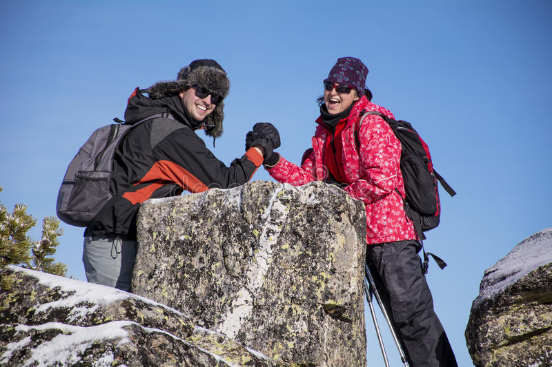 Smiling Equipped hiker woman and young man arm wrestling. Equipped hiker women and young men arm wrestling on a rocks in a winter mountain royalty free stock photos