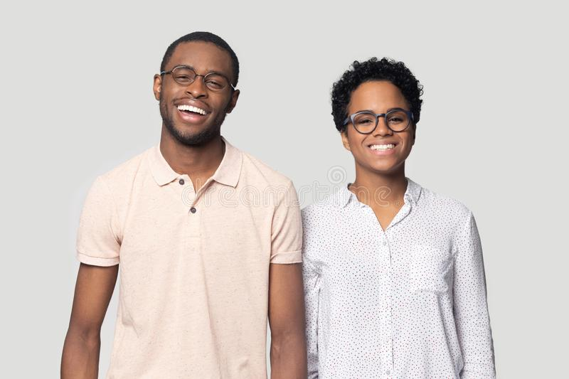 Smiling ethnic couple laugh posing for picture in studio. Portrait of smiling african American man and woman stand isolated on grey studio background look at stock images