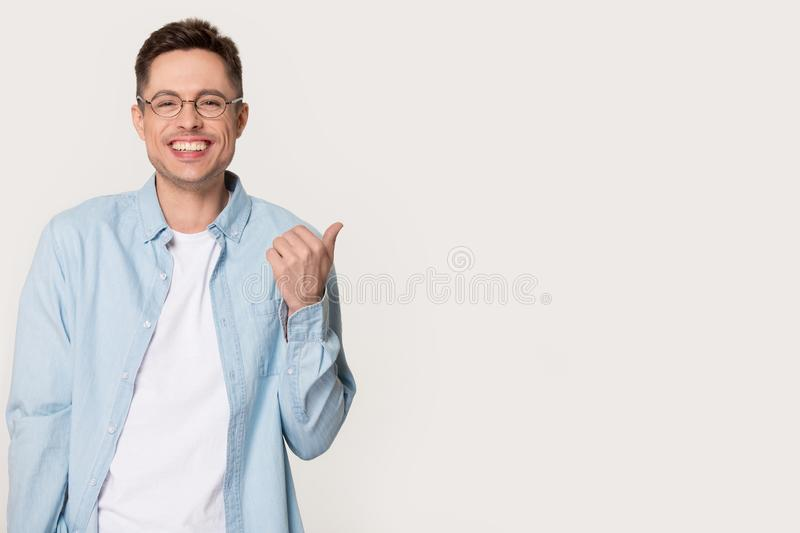 Smiling man in glasses point with finger on copy space. Smiling European male client in glasses and shirt isolated on grey studio background show good deal or stock image