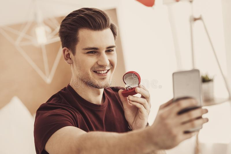 Smiling excited man making selfie with expensive wedding ring stock photos