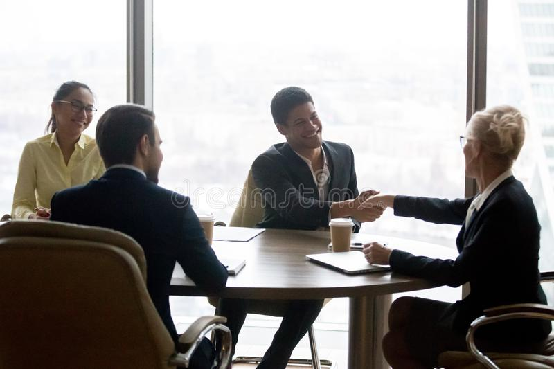 Smiling executive businesswoman handshaking african businessman at group meeting royalty free stock photography