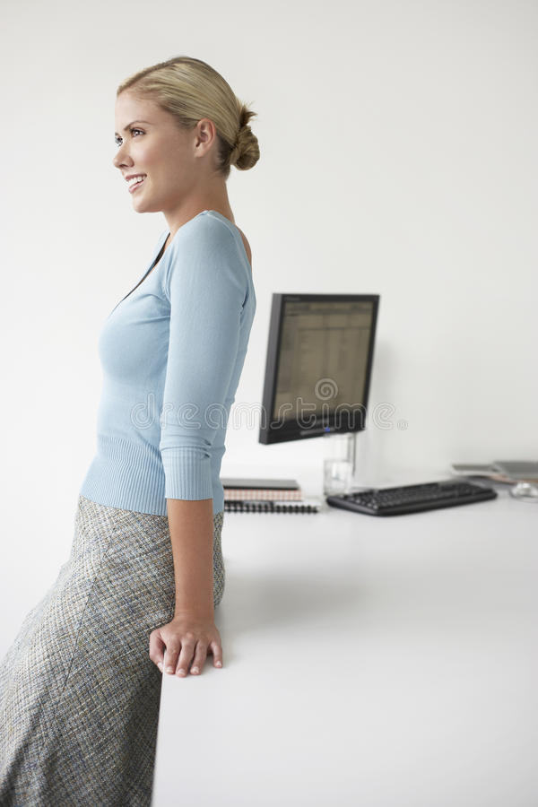 Smiling Executive Leaning On Office Desk stock photography