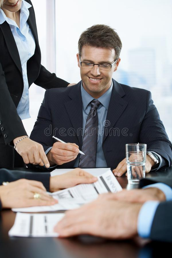 Smiling executive signing contract. In office, assistant pointing at paper stock photos