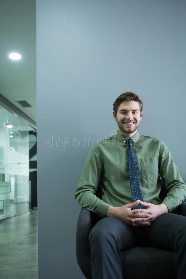Smiling executive sitting on chair in waiting area royalty free stock photos
