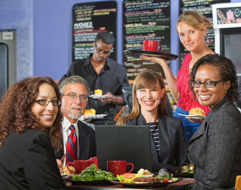 Smiling Executives with Barista. Smiling executives with attractive server in coffee house royalty free stock photo