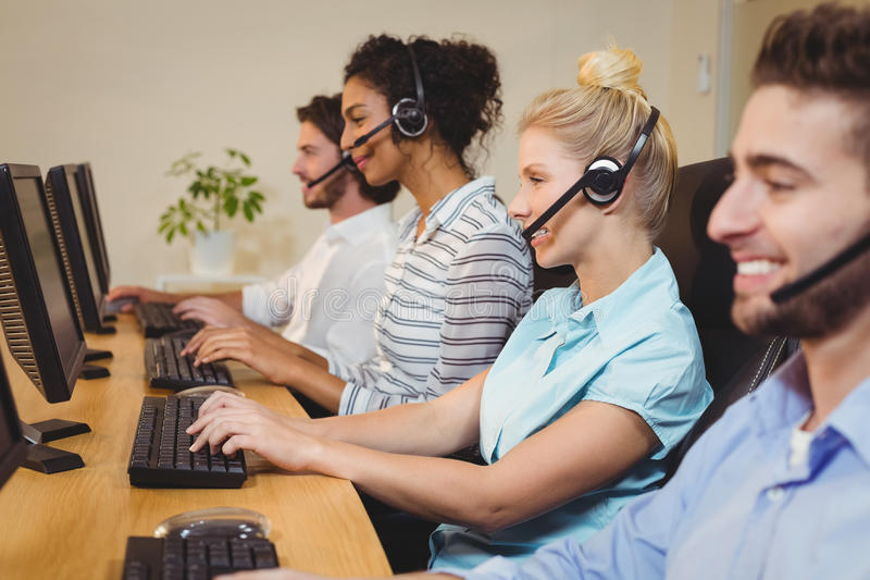 Smiling executives working in call center. Wearing headsets stock images