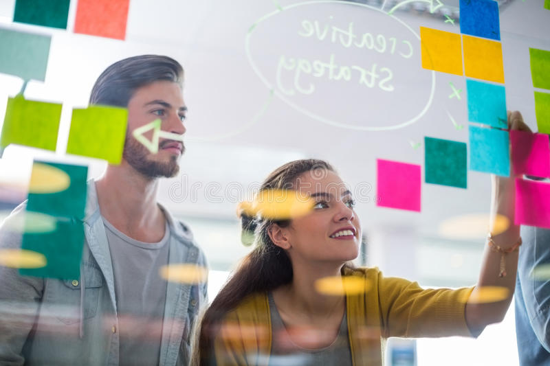 Smiling executives writing on sticky notes on glass wall royalty free stock photo
