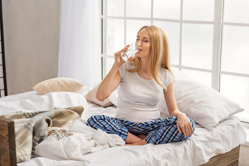 Smiling expectant female drinking water royalty free stock image