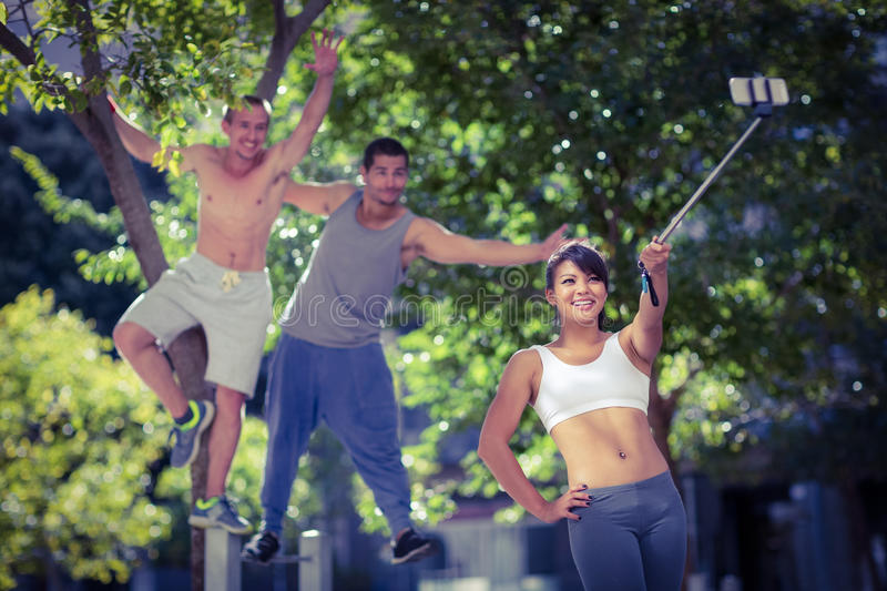Smiling extreme athletes taking selfies with selfiestick stock images
