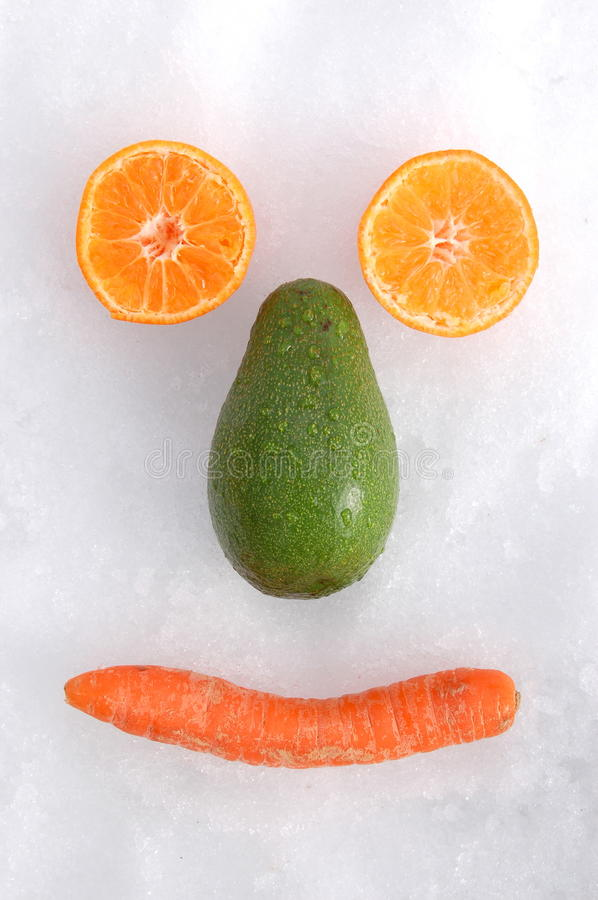 Smiling face. Made of avocado, carrot and tangerine on the snow stock photos