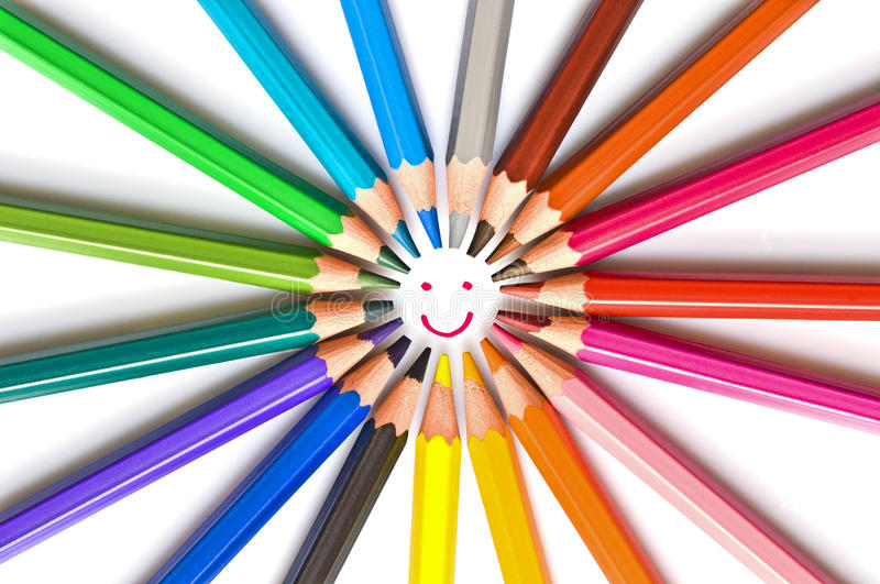 Smiling face drawn in a circle of colorful wooden pencils isolated on white, school art and education concept stock photo