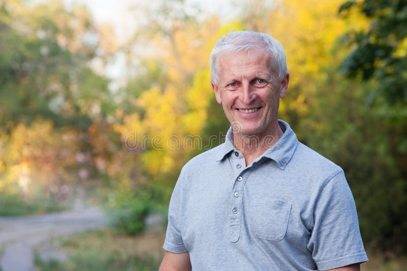 Smiling face of grey-haired old man stock images