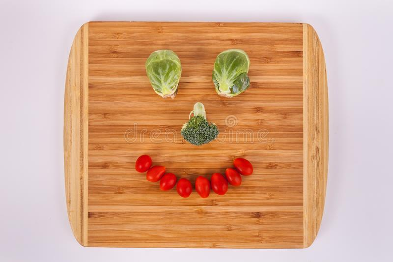 Smiling face made of Brussel sprouts broccoli floret cherry tomatoes stock photos