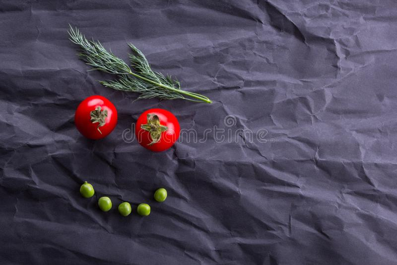 Smiling face from vegetables on black paper background stock photo