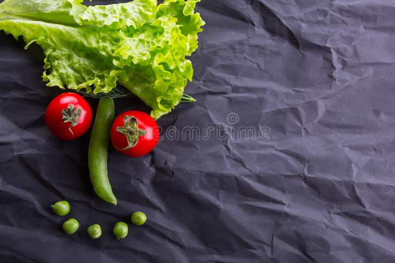 Smiling face from vegetables on black paper background. With space for text stock image