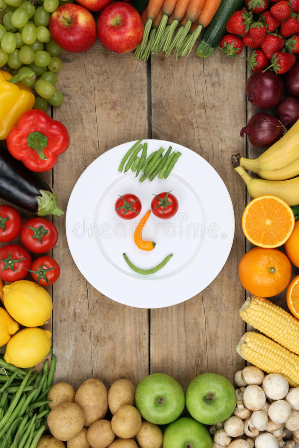Smiling face from vegetables and fruits on plate with tomatoes a royalty free stock images
