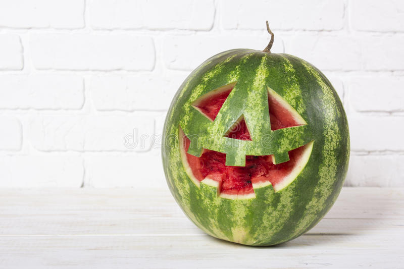 Smiling face of a water-melon on a Halloween like a pumpkin for. Halloween royalty free stock photos