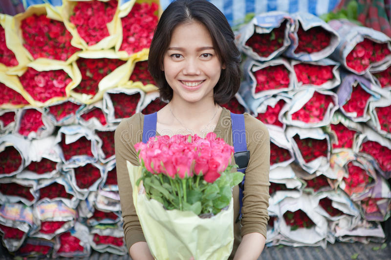 Smiling face of younger asian woman with pink roses flower bouquet in hand stock images
