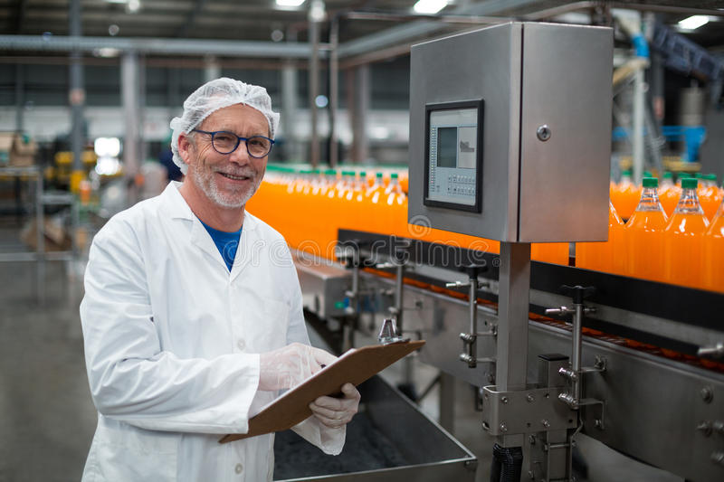 Smiling factory engineer maintaining record on clipboard in factory. Portrait of smiling factory engineer maintaining record on clipboard in drinks production stock images