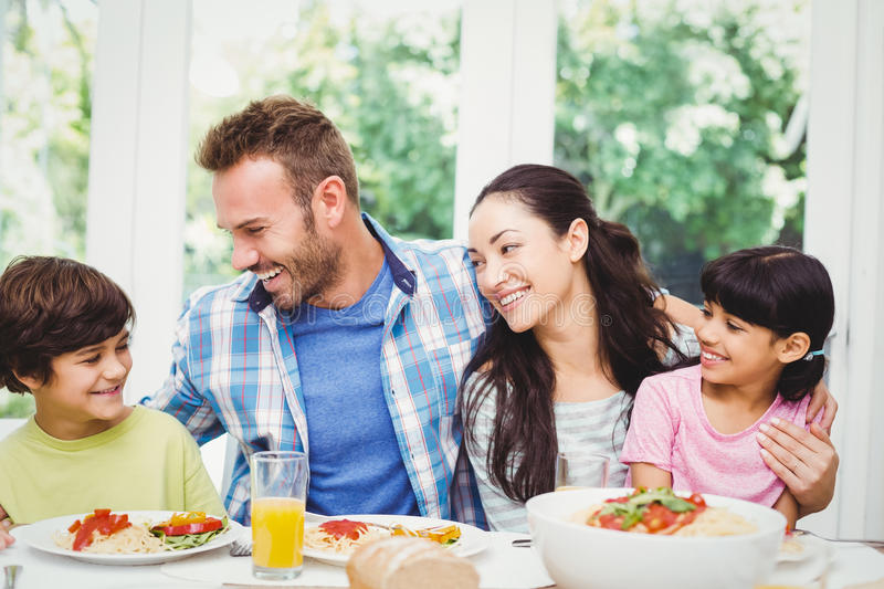 Smiling family with arm around while sitting at dining table. With food in home royalty free stock photography