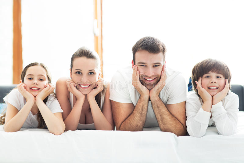 Download Smiling family in bed stock photo. Image of comfortable - 54321136